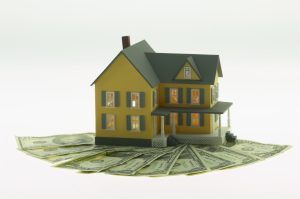Cutout of miniature house and dollar bills